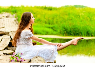 dancer sits on a bridge and pulling sock feet