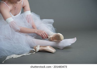 dancer wears pointes,sitting on the floor on a grey background
