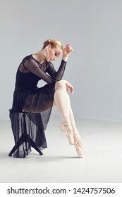 Dancer woman in black dress posing sitting on a chair
