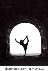 Dancer, woman dancing in the arch,ballet dancer.Woman doing yoga in the old fortification place.Contrast, silhouette of girl figure on sunny day. Woman figure.Black and white photo.Yoga exercise