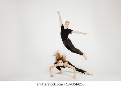 Dancer Woman and Man in Dynamic Action Figure Pose. Beautiful Modern Jazz Dance Couple in Black Picture in Motion Isolated on White Background. Muscular Male Perfomer do Soubresaut Jump