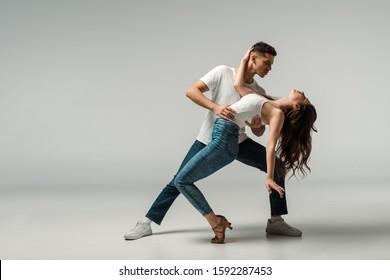 dancers in denim jeans dancing bachata on grey background
