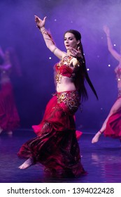 Dancers with long hair in red oriental costumes dance belly dance on the concert stage
