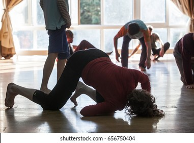dancers moving on floor on class. Dancers lean on floor, silhouette on blurred background,