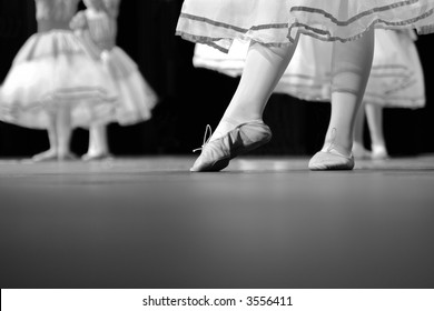 Dancers on stage during a recital. Originally shot in Black and White. Noise reduction was applied on the floor and the dancers in the background but not the foreground dancer.