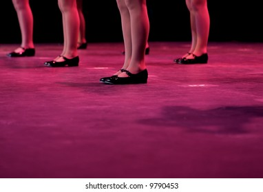 Dancers on stage during a recital in bright costumes. Noise reduction was applied on the floor and the dancers in the background but not the foreground dancers.