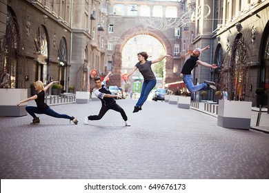 Dancers on the street, two boys and  two girls jumping and dancing on city streets