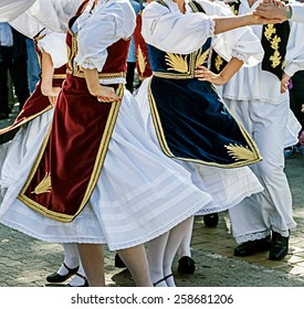 Dancers in traditional costumes who perform the movements of a serbian dance.