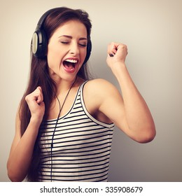 Dancing active young woman in headphones singing the song. Vintage portrait