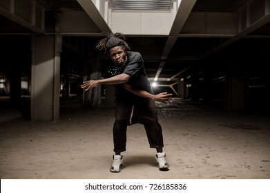 Dancing african american man with dreadlocks and in black clothes and white sport shoes on the dark background. Full length