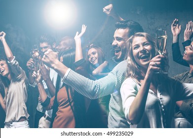 Dancing all night long. Group of beautiful young people dancing with champagne flutes and looking happy