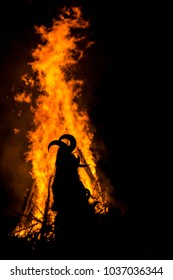 Dancing around the huge ritual fire in mask with horns