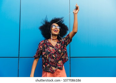 Dancing attractive afro american woman in sunglasses, listening to music in earphones on cellphone. Dressed in vivid blouse, with short curly hairstyle. Outdoors.
