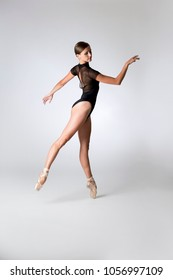 Dancing ballerina wearing a black mesh-back leotard