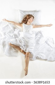Dancing ballet dreamer dressed in white with white sheets, studio shot on white background. Expressive woman in action, dreaming concept. Dreaming of becoming professional dancer.