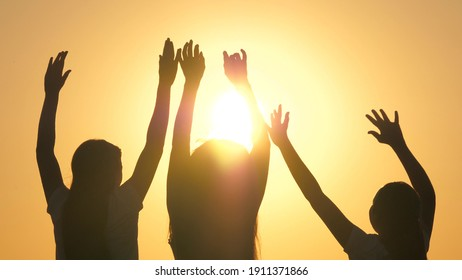 Dancing at beach party, women having fun and celebrating in sun by sea. Girls are dancing cheerfully on a summer evening at sunset. Free teens having fun raise their hands up. Fun, holiday, weekend