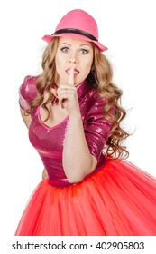 Dancing Blonde girl wearing in pink costume with wide eyed asking for silence or secrecy with finger on lips hush hand gesture. Isolated over white background