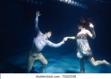 Dancing couple under water in swimming pool