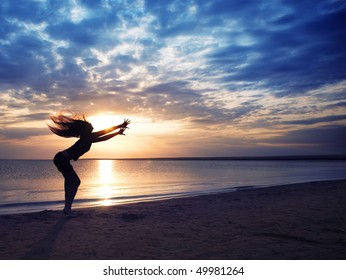 Dancing dynamic woman at the beach during sunset