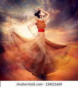 Dancing Fashion Woman wearing Blowing Long Chiffon Dress. Fashion Art Fantasy Collage. Sand Fairy