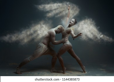 Dancing in flour concept. Girl woman female wearing white dress and guy man male making dance element in flour / white dust in form of wings as angels on isolated black / grey background