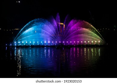 A dancing fountain, or fountain, formed by a controlled ascending and descending rainbow-like lights.  And the color reflecting on the water.