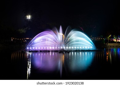 A dancing fountain or a fountain that is formed by controlling the ups and downs and has a light tone bright blue and pink.  And the color reflecting on the water.