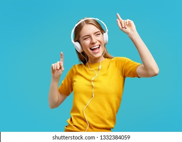 Dancing girl listens to music in earphones, enjoys the song. Photo of funny girl in yellow sweater on blue background