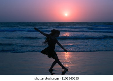 Dancing girl on the seaside. Elegant and light moves during sunset, purple glow illuminates the silhouette.