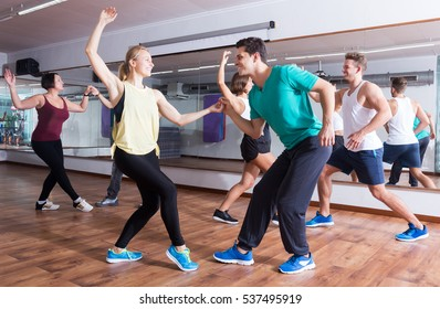 Dancing happy couples learning swing at dance class
