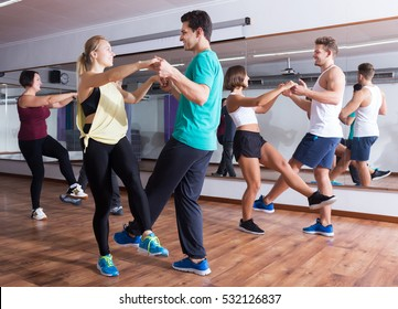 Dancing happy young couples learning swing at dance class