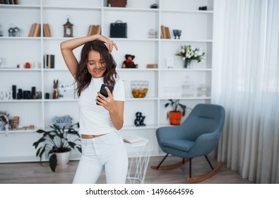 Dancing and having fun. Woman in white clothes with her smartphone resting in living room. - Shutterstock ID 1496664596
