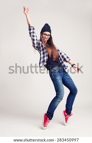 d23d74ecf0e Dancing hipster girl in glasses and black beanie on light grey background