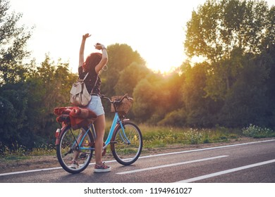 Dancing on the nature. Beautiful smiling hipster girl listening favorite music on retro bike
