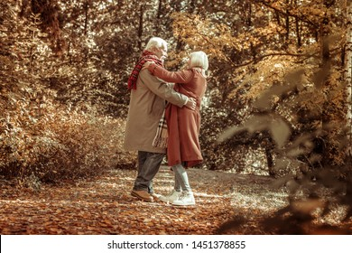 Dancing in a park. Happy smiling senior man hugging his beautiful wife standing in a parkway and pretending to dance.