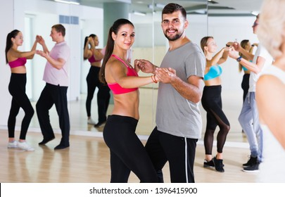 Dancing positive swiss couples learning salsa at dance class