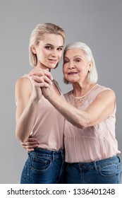 Dancing posture. Positive tall blonde girl connecting hands and body with old woman while preparing for waltz