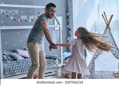 Dancing with princess. Full length of father and daughter holding hands and smiling while dancing in bedroom