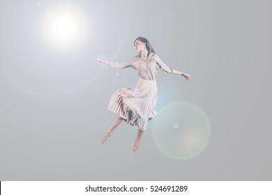 Dancing queen. Studio shot of attractive young woman in beautiful dress hovering in air
