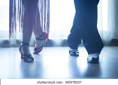 Dancing shoes feet and legs of female and male couple ballroom and latin salsa dancer dance teacher in dance school rehearsal room class.