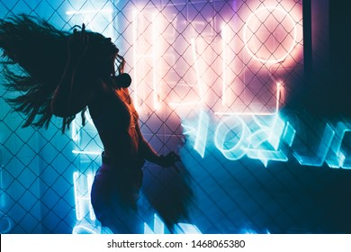 Dancing silhouette of girl in a nightclub. Attractive dancing girl in the club, hair flying, neon light, motion effects.