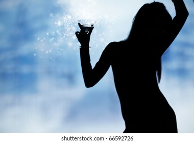 dancing silhouettes of women with champagne  in a nightclub