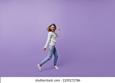 Dancing Slavic female student in stylish jeans and winter sweater moves on purple background. Brunette with headphones poses for full-length photo