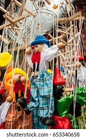 Dancing strings wooden puppet clowns and pinocchios toys hanging in a stand.