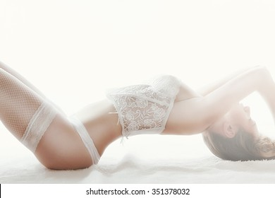 Dancing striptease laying on back Girl in white lingerie corset stockings panties long white pearl beads face covered by hair