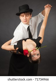 Dancing tango pair, girl holding red rose in mouth