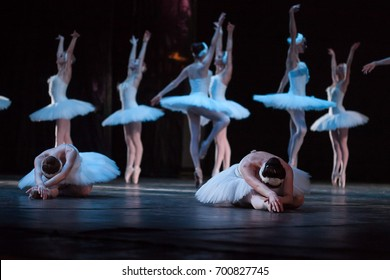 dancing, tradition, advancement concept. on the stage of the theater group of female ballet dancers in white tutus and leotards, two of them fell down and others dancing on the tips of their toes