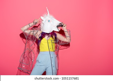 dancing woman in fashionable transparent raincoat and unicorn mask on red