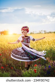 Dancing woman in the field. She is wearing traditional Eastern Europe folk costumes.