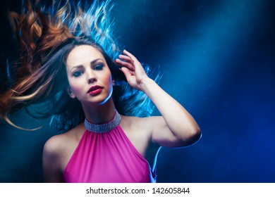dancing woman in pink dress and  hair in motion   studio shot